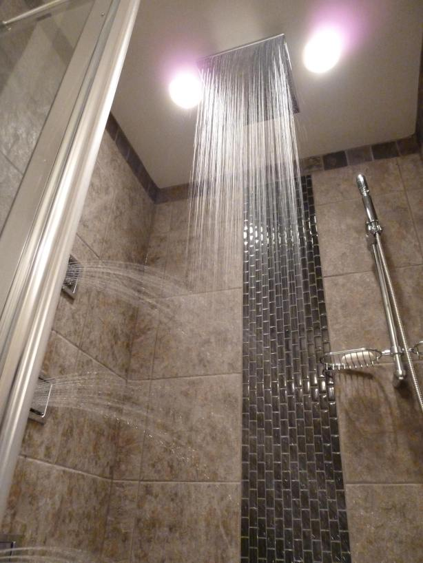 nice-rain-shower-head-in-the-bathroom-blended-with-brown-ceramic-wall-together-with-ceiling-lamps